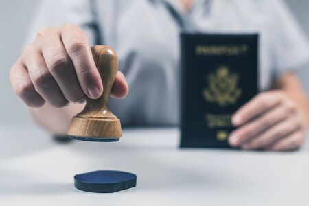 Immigration and passport control at the airport. woman border control officer puts a stamp in the US passport of american citizen. Concept 写真素材