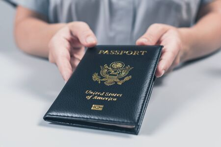 Immigration and passport control at the airport. woman border control officer with US passport of american citizen. Concept