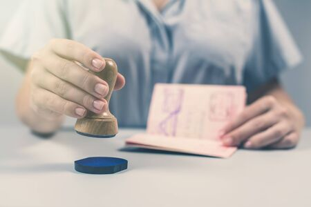 Immigration and passport control at the airport. woman border control officer puts a stamp in the passport. Concept