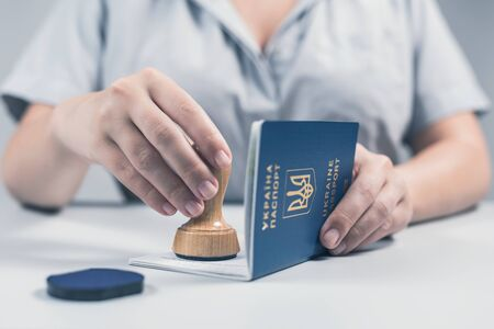 Immigration and passport control at the airport. woman border control officer puts a stamp in the Ukrainian passport. Concept Фото со стока
