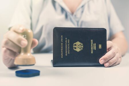 Immigration and passport control at the airport. woman border control officer puts a stamp in the Deutsch passport of German citizen. Concept