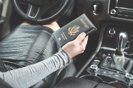 Border control concept.  Woman holding american passport sitting on drivers seat in car for check customs officers