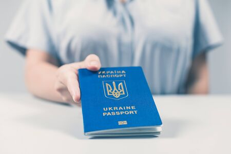 Immigration and passport control at the airport. woman border control officer with Ukrainian passport. Concept 写真素材