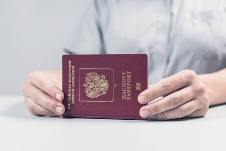 Immigration and passport control at the airport. woman border control officer puts a stamp in the Russian passport. Concept 写真素材