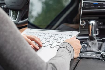 woman watching and using laptop while sitting on drivers seat in car. Crop image. Concept.