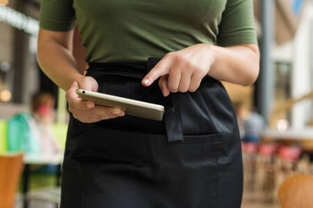 Cropped image of woman waitress in apron ready to take order using notepad or tablet, and pen in cafe.