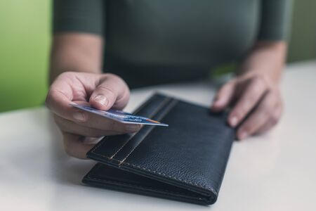 Cropped image of  woman hands with folder and bill on the table of cafe. visitor of restaurant ready to pay by credit card Stock fotó
