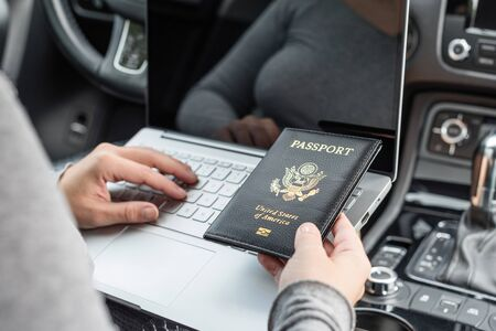 Woman in the car with laptop and american passport. Business concept.