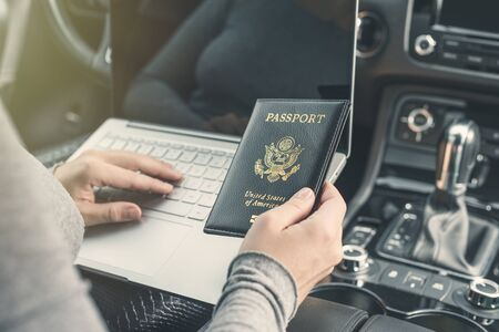 Woman in the car with laptop and american passport. Travel concept.