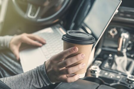 woman watching and using laptop while sitting on drivers seat in car and drinking coffee from paper cup. Crop image. Concept.