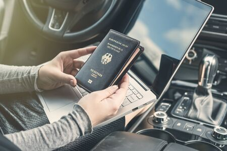 Woman in the car with laptop and germany passport. Travel concept.