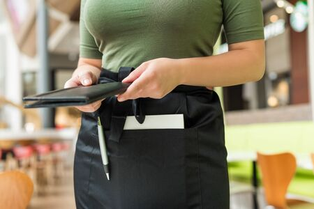Cropped image of woman waitress in apron hold out bill folder to cafe visitor of cafe or restaurant.