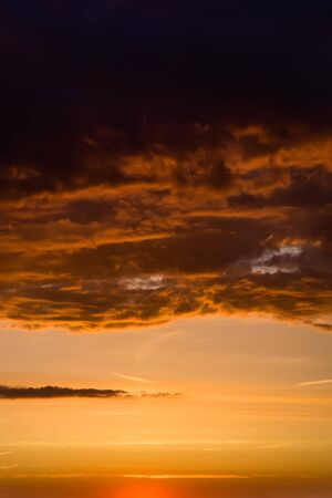Stormy dramatic sky background with yellow red and orange clouds. Sunset skyline. Storm on the beach. Vertical size