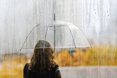 Una silhouette di donna con ombrello trasparente attraverso la finestra bagnata con gocce di pioggia. Autunno
