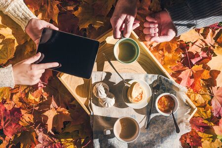 Couple of young people are taking a picture on a tablet of morning breakfast on a wooden tray in the autumn park with colorful maple leaves. Aerial view Stock Photo