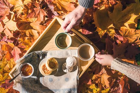Couple of man and woman having morning breakfast in the autumn garden with colorful maple leaves. cup of coffee, marshmallow jam and a cheese pancake on a wooden tray.  Aerial view Stockfoto