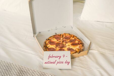 Open box of pizza on the big bed and card with text february 9 - national pizza day. Concept