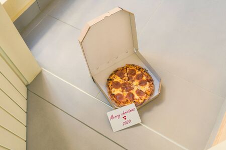 Open box of pizza and card with text merry christmas 2020 on home doorstep on front porch. Delivery. Concept