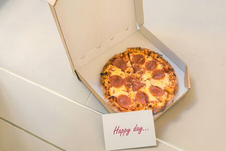 Open box of pizza and card with text happy day on home doorstep on front porch. Delivery. Concept