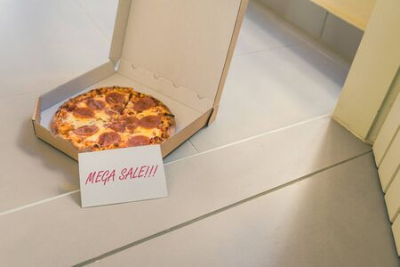 Open box of pizza and card with text: mega sale on home doorstep on front porch. Delivery. Concept