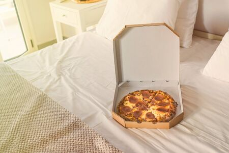 Open box of pizza on the big bed. Concept