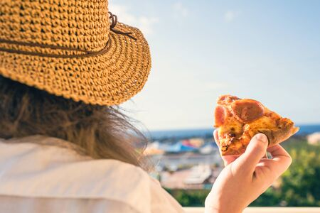 Girl in a straw hat with a slice of pizza at the resort on the background of the sea