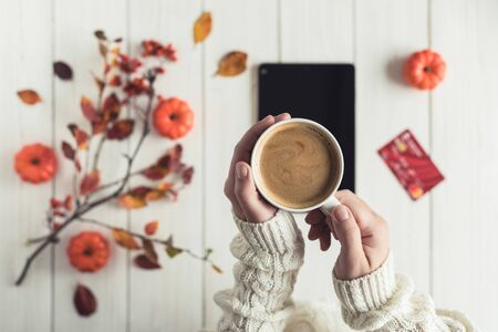 Woman with tablet and credit (discount) card cup on white retro wood boards. Coffee, tablet, leaves, rowan and small pumpkins . Autumn, fall concept. Flat lay, top view.