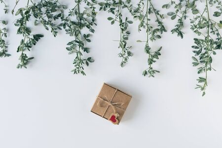 gift in a box of kraft paper on white wood table. Green leaves, branches. concept. Flat lay, top view.