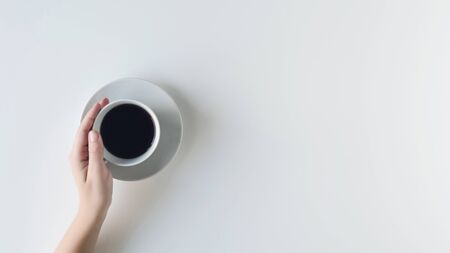 girl hands holding cup with black coffee on the white table. flat lay, top view. coffee art