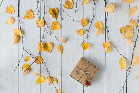 packing gift in a box of kraft paper on white retro wood boards. leaves, birch branches. Thanksgiving. Autumn, fall concept. Flat lay, top view.  Banco de Imagens