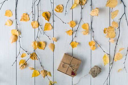 Woman packing gift in a box of kraft paper on white retro wood boards. leaves, birch branches. Thanksgiving. Autumn, fall concept. Flat lay, top view.