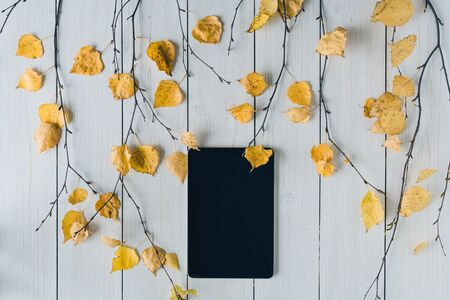 tablet with birch branches with yellow leaves  on white retro wood boards. background. Autumn, fall concept. Flat lay, top view. Banco de Imagens