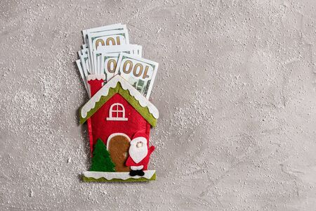 Bundle of US dollars in the funny santa claus house from felt on the gray concrete background. Cristmas Concept.