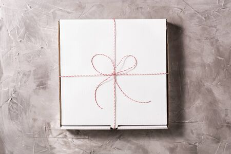 Closed box of pizza tied of christmas red white string or twine in a bow on the on grey concrete background. Concept