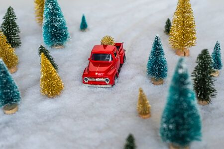 Creative Christmas decoration with red truck and colorful snowy spruces in the snow. Winter forest. Aerial, top view. Flat lay