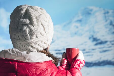Back view of young woman in a winter knitted white cap, jacket and Christmas gloves drinking hot coffee or chocolate from red cup in the snowy mountains.