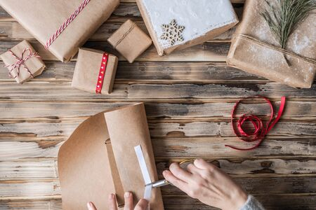 Woman packing handmade gifts made from kraft paper, christmas rope, fir branches on the rustic wood planks background. DIY. Flat lay. Stock fotó