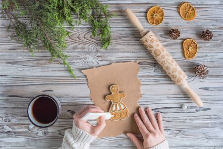 Woman decorating honey gingerbread men on wooden grey table and craft paper. Christmas Icing bakery. Flat lay Stock Photo