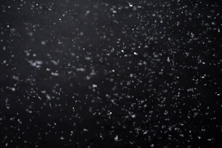 Falling  snow at night. Bokeh lights on black background, flying snowflakes in the air. Overlay texture. Snowstorm Stock Photo