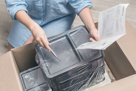 Woman shopper sitting on floor at home opening carton box holding invoice and stationery knife received parcel package from internet shop. Delivery service. Top view.