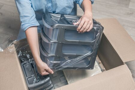 Woman shopper sitting on floor at home opening carton box using stationery knife received parcel package from internet shop. Delivery service. Top view. Stockfoto