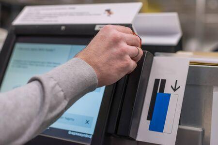 Homme payant au comptoir libre-service à l'aide de l'écran tactile et de la carte de crédit. Caissier ou terminal libre-service isométrique. Banque d'images