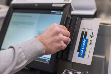 Homme payant au comptoir libre-service à l'aide de l'écran tactile et de la carte de crédit. Caissier ou terminal libre-service isométrique.