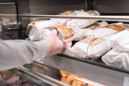 Man buying bread in a pastry shop for Christmas