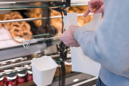Man buying pretzels in a pastry shop for Christmas