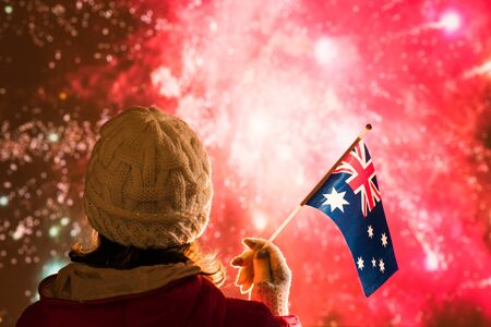 Fireworks at night. Woman in winter clothes with Australian flag on the New Year. Stock Photo