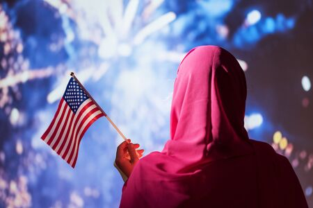 Muslim woman in a scarf holding American flag  during fireworks at night.