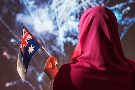 Muslim woman in a scarf holding Australian flag  during fireworks at night. Stock Photo
