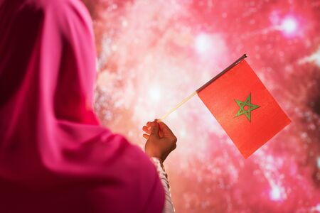Muslim woman in a scarf holding flag of Morocco during fireworks at night.