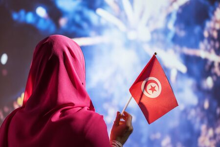 Muslim woman in a scarf holding flag of Tunisia during fireworks at night.
